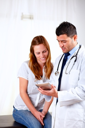 Portrait of a latin doctor and a female patient looking something on tablet PC at hospital
