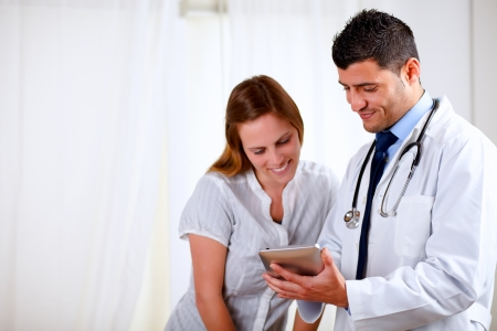 Portrait of a handsome doctor and a patient woman looking something on tablet PC at hospital