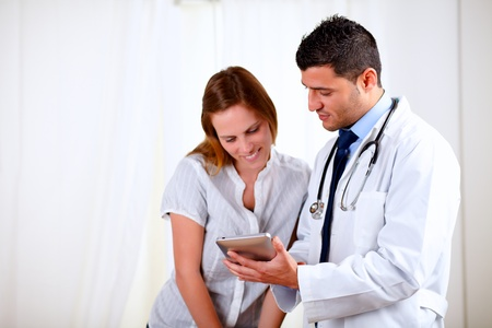 Portrait of a handsome doctor and a female patient looking something on tablet PC at hospital Stock Photo