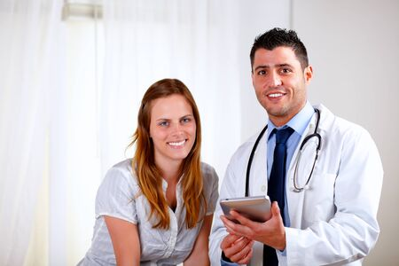 Portrait of a young blonde patient woman with her medical doctor looking at you at hospital indoor photo