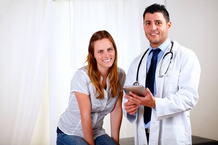 Portrait of a young pretty patient woman with her medical doctor looking at you at hospital indoor photo
