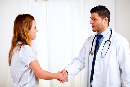 Portrait of a medical specialist greeting a beautiful patient at hospital indoor photo