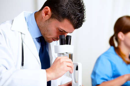 Portrait of a attractive latin doctor using a microscope at laboratory at hospital indoor photo