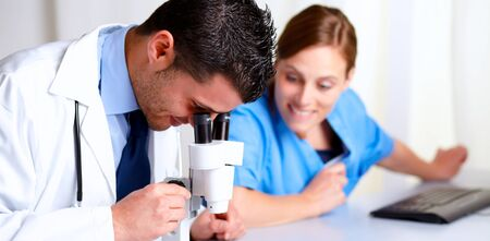 Portrait of a handsome medical doctor using a microscope with a pretty and happy nurse at hospital photo