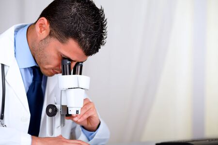 Portrait of a attractive hispanic doctor using a microscope at laboratory at hospital indoor photo