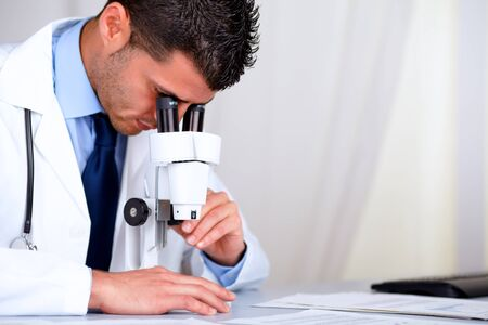 Portrait of a young attractive doctor working with a microscope at laboratory at hospital indoor photo