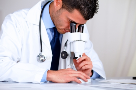 Portrait of a hispanic professional doctor with a microscope at laboratory at hospital indoor photo