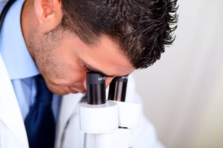 Closeup portrait of a Professional medical man using a microscope photo