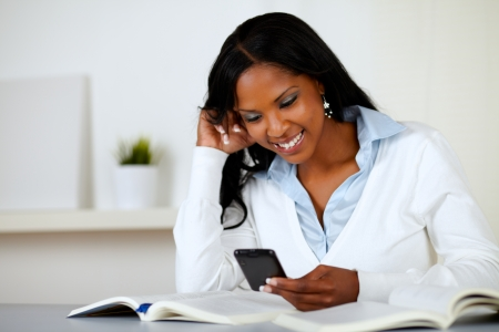 Portrait of a pretty lovely woman smiling and reading a cellphone message at soft colors composition photo