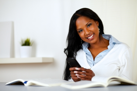 Portrait of an afro-american young woman, smiling and looking to you while is using a cellphone at home indoor photo