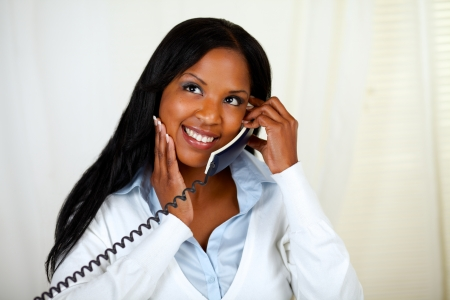 conversing: Portrait of a young black lady thinking and conversing on phone