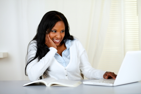 student with laptop: Portrait of a lovely student girl smiling and looking to laptop at home indoor Stock Photo