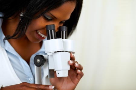 Portrait of a beautiful afro-american black woman using a microscope at soft colors composition photo