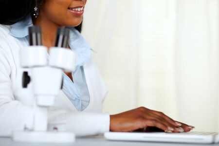 Portrait of a beautiful black young woman working on laptop at laboratory photo