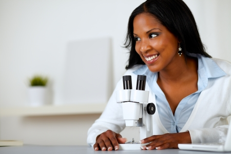 Portrait of a pretty black woman working with a microscope at laboratory photo