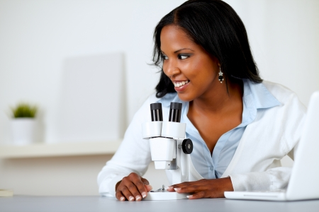 Portrait of a pretty black female working with a microscope at laboratory photo