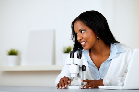 Portrait of a charming young woman using a microscope while looking to his right photo