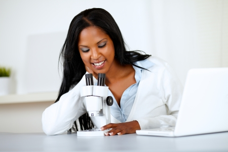 Portrait of an attractive african woman working with a microscope and a laptop at soft colors composition photo