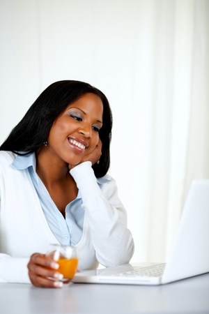 Portrait of a charming and relaxed woman smiling and reading on laptop screen at soft composition Stock Photo - 14463534