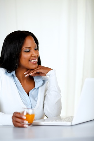 Portrait of a pretty young woman smiling and reading on laptop screen at soft composition photo