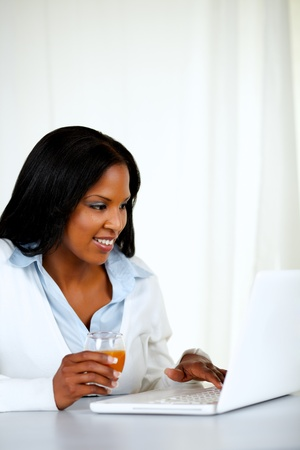 Portrait of a pretty woman smiling and using a laptop while drinking an healthy orange juice at soft composition photo