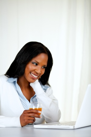 Portrait of a pretty relaxed female smiling and reading on laptop screen at soft composition photo