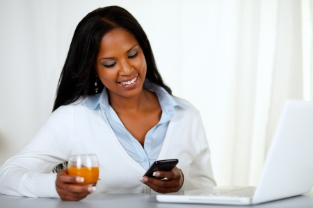 Portrait of a young woman sending a message by the mobile at home indoor photo