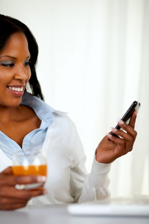 Portrait of a young woman sending a message by cellphone at home indoor photo