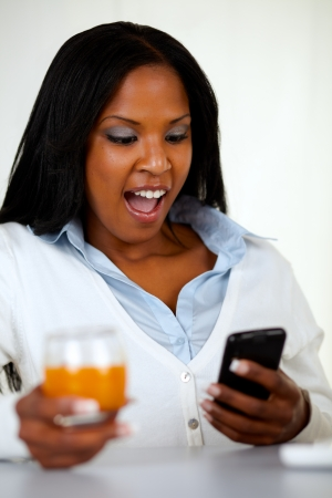 Portrait of a surprised young woman reading a message on mobile at soft composition photo