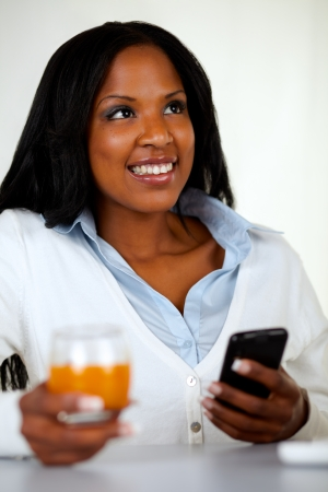 Portrait of a beautiful woman smiling while is using a cellphone and looking up at soft composition photo