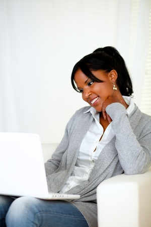 Portrait of a lovely young woman smiling and looking to laptop screen at home indoor Stock Photo - 14546486