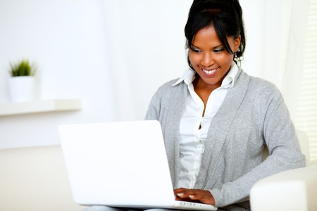 Portrait of a smiling young woman using laptop while is sitting on sofa at home indoor Stock Photo - 14547732