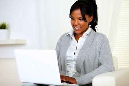 Portrait of a smiling woman using laptop while is sitting on sofa at home indoor Stock Photo - 14547733