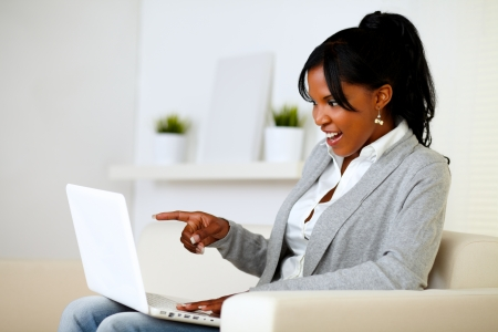 Portrait of a surprised woman pointing to laptop screen while is sitting on sofa at home Stock Photo - 14546485