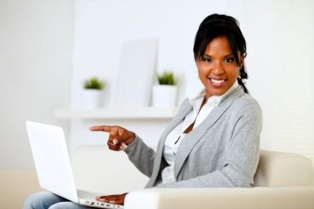 Portrait of an afro-american woman pointing to laptop screen while looking to you Stock Photo - 14547728