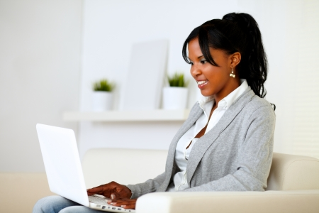 Portrait of an afro-american woman using laptop while is sitting on sofa at home indoor photo