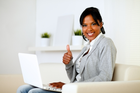 Portrait of a positive afro-american woman looking to you while is working on laptop and lifting the finger up Stock Photo - 14547729