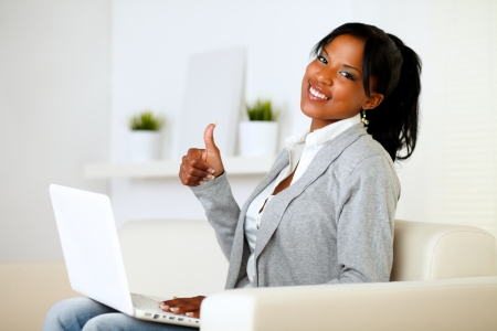 Portrait of a positive afro-american young woman looking to you while is working on laptop and lifting the finger up at home photo