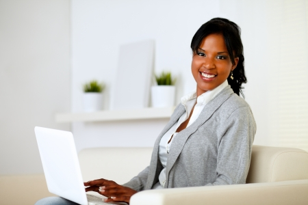 Portrait of a happy woman browse the Internet on laptop while is sitting on sofa at home Stock Photo - 14546492