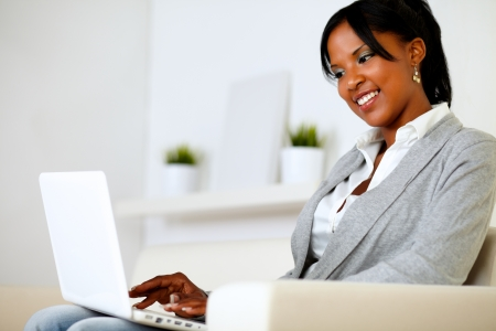 Portrait of a beautiful young woman working on laptop while sitting on sofa at home Stock Photo - 14547724