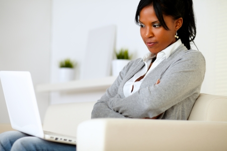 Portrait of a reflective young woman reading on laptop screen at home Stock Photo - 14547722