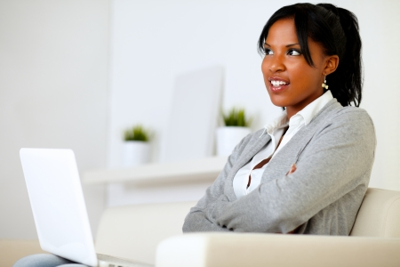 Portrait of a pensative young woman sitting on sofa with a laptop at home indoor Stock Photo - 14547725