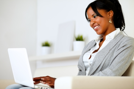 Portrait of an afro-american young woman using laptop at home indoor Stock Photo - 14547720