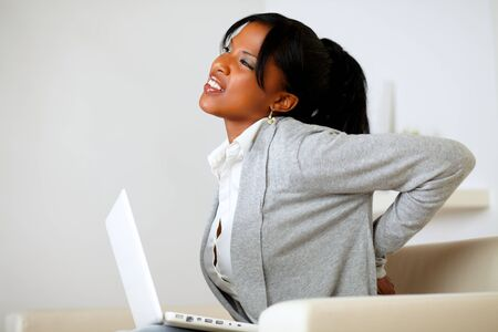 Portrait of an afro-american young woman with back pain sits down on sofa at home Stock Photo