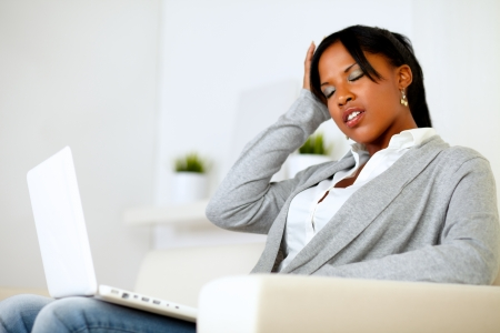 Portrait of an afro-american tired young woman with headache while is sitting on sofa at home Stock Photo - 14547723