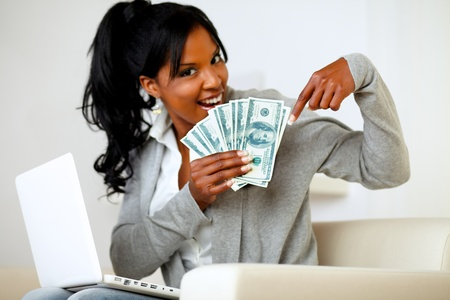 Portrait of a happy young woman pointing plenty of cash money photo
