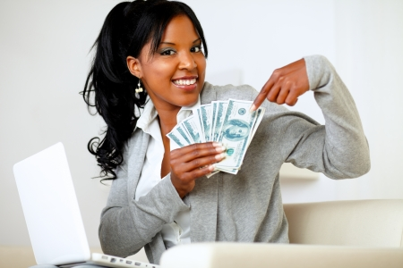 Portrait of a happy woman pointing plenty of cash money photo