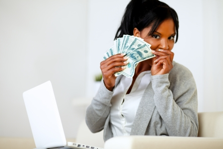 Portrait of an ambitious excited black woman with money photo