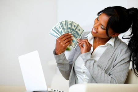 Portrait of a happy woman looking to dollars at soft colors composition Stock Photo
