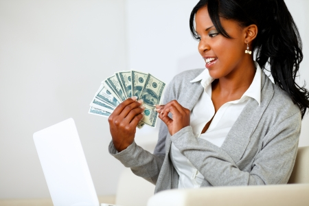 Portrait of a beautiful woman looking to dollars at soft colors composition photo